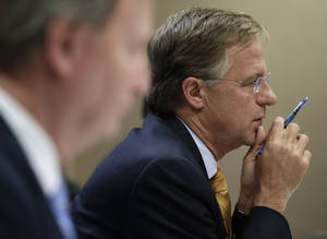 Photo -   Tennessee Gov. Bill Haslam, right, listens to a presentation by the Department of Children's Services during budget hearings on Thursday, Nov. 8, 2012, in Nashville, Tenn. Haslam has asked state departments to develop plans for a 5 percent spending cut. (AP Photo/Mark Humphrey)