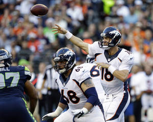 Photo - ADVANCE FOR WEEKEND EDITIONS, JAN. 25-26 - FILE - In this Aug. 17, 2013, file photo, Denver Broncos quarterback Peyton Manning (18) passes as Zane Beadles (68) blocks in the first half of a preseason NFL football game against the Seattle Seahawks in Seattle. The two teams are slated to meet in Super Bowl XLVIII on Sunday, Feb. 2, 2014, in East Rutherford, N.J. (AP Photo/Elaine Thompson, File)