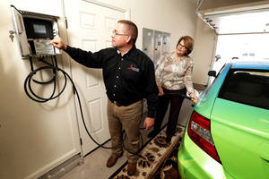 Photo - Dan Reeves of Landmark Fine Homes and Pam Hall of Oklahoma Natural Gas fill a CNG vehicle in the garage at the Landmark model home at 4500 Northfields in Norman.