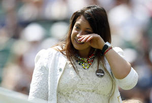 Photo - 2013 Wimbledon champion Marion Bartoli of France wipes her eyes as she arrives on court to take part in the coin toss for the match between Julia Glushko of Israel and Sabine Lisicki of Germany at the All England Lawn Tennis Championships in Wimbledon, London, Tuesday, June 24, 2014. Traditionally the reigning champion would play her first match on Centre Court but due to Bartoli's retirement the runner up Lisicki will open play. (AP Photo/Sang Tan)