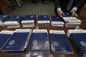 Photo - Copies of President Barack Obama's proposed fiscal 2015 budget are set out for distribution by Senate Budget Committee Clerk Adam Kamp, on Capitol Hill in Washington, Tuesday, March 4, 2014.  President Barack Obama is unwrapping a nearly $4 trillion budget that gives Democrats an election-year playbook for fortifying the economy and bolstering Americans' incomes. It also underscores how pressure has faded to launch bold, new attacks on federal deficits.   (AP Photo/J. Scott Applewhite)