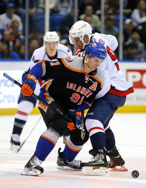 photo - New York Islanders center John Tavares (91) battles for the puck with Washington Capitals center Mike Ribeiro (9) during the first period of an NHL hockey game at the Nassau Coliseum in Uniondale, N.Y., Saturday,  March 9, 2013. (AP Photo/Paul J. Bereswill)