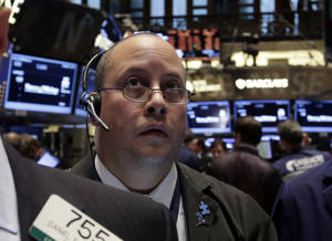 Photo - FILE - In this Oct. 31, 2013, file photo, Trader Jeffrey Vazquez works on the floor of the New York Stock Exchange. Stock futures are heading lower after U.S. policy makers said they would maintain a massive economic stimulus program. (AP Photo/Richard Drew, File)