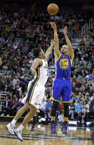 Photo - Utah Jazz's Trey Burke, left, defends against Golden State Warriors' Stephen Curry (30) as he shoots in the first quarter of an NBA basketball game Friday, Jan. 31, 2014, in Salt Lake City. (AP Photo/Rick Bowmer)