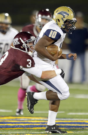 Photo - Southmoore's Peirce Spead gts by Edmond Memorial's Charlie Dutton during the high school football game between Edmond Memorial and Southmoore at Wantland Stadium in Edmond, Okla., Friday, Oct. 19, 2012. Photo by Sarah Phipps, The Oklahoman