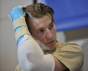 Photo - Retired Infantryman Brendan M. Marrocco uses his transplanted arm to brush his hair back during a news conference Tuesday, Jan. 29. 2013 at Johns Hopkins hospital in Baltimore.  Marrocco received a transplant of two arms from a deceased donor after losing all four limbs in a 2009 roadside bomb attack in Iraq. (AP Photo/Gail Burton)