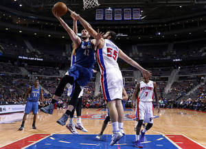 Photo - Minnesota Timberwolves power forward Kevin Love (42) drives on Detroit Pistons power forward Josh Harrellson (55) in the first half of an NBA basketball game in Auburn Hills, Mich., Tuesday, Dec. 10, 2013. (AP Photo/Paul Sancya)
