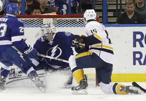 Photo - Nashville Predators center Craig Smith (15) fires the puck past Tampa Bay Lightning goalie Anders Lindback (39), of Sweden, for a goal during the second period of an NHL hockey game, Thursday, Dec. 19, 2013, in Tampa, Fla. (AP Photo/Chris O'Meara)