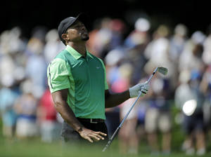 Photo - Tiger Woods reacts on the 17th fairway during the first round of the Quicken Loans National golf tournament, Thursday, June 26, 2014, in Bethesda, Md. (AP Photo/Nick Wass)