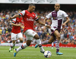 Photo - Arsenal's Alex Oxlade-Chamberlain, left, vies for the ball with Aston Villa's Karim El Ahmadi during the English Premier League soccer match between Arsenal and Aston Villa at the Emirates Stadium in London, Saturday, Aug. 17, 2013. (AP Photo/Kirsty Wigglesworth)