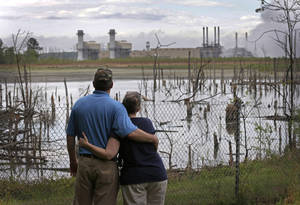Photo - In this April 25, 2014 photo, Bryant Gobble, left, hugs his wife, Sherry Gobble, right, as they look from their yard across an ash pond full of dead trees toward Duke Energy's Buck Steam Station in Dukeville, N.C. Records obtained by The Associated Press show that Duke and North Carolina environmental regulators have known since 2011 that groundwater samples taken from monitoring wells near several homes in Dukeville contained substances, some that can be toxic, exceeding state standards. (AP Photo/Chuck Burton)