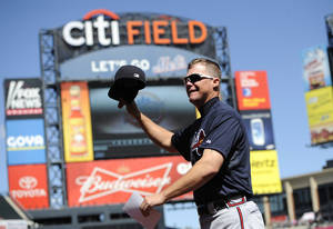 Photo -   Atlanta Braves third baseman Chipper Jones waves his hat to the cheers of fans as he runs back to the dugout after bringing the lineup card to the umpires before a baseball game against the New York Mets, Sunday, Sept. 9, 2012, at Citi Field in New York. Jones is retiring after the season and it was his last game at Citi Field. (AP Photo/Kathy Kmonicek)