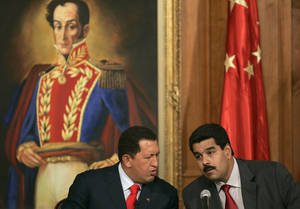 photo - FILE .- In this Oct. 17, 2006 file photo Venezuelan President Hugo Chavez, left, talks with his then Foreign Minister and current Vice-President Nicolas Maduro during a meeting with Chinese businessmen at Miraflores Palace in Caracas, Venezuela.  Chavez is to return to Cuba Sunday for another surgery in his battle against cancer, which has led him to speak publicly of a successor for the first time.  Chavez said Saturday that if there are &quot;circumstances that prevent me from exercising the presidency further&quot;  Vice-President Nicolas Maduro should replace him for the remainder of his term. (AP Photo/Fernando Llano, File)