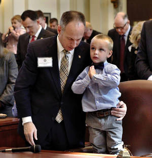 photo - Rep. Jeff Hickman stands with his son, Austin Hickman, 3, during an invocation before newly elected Oklahoma representatives took the oath of office on Wednesday at the Capitol.   Photo by Jim Beckel, The Oklahoman