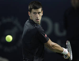 Photo - Novak Djokovic of Serbia returns the ball to Denis Istomin of Uzbekistan during the second round of the Dubai Duty Free Tennis Championships in Dubai, United Arab Emirates, Tuesday, Feb. 25, 2014. (AP Photo/Kamran Jebreili)