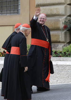 photo - Cardinal Timothy Dolan waves to reporters as he arrives for a meeting at the Vatican, Friday, March 8, 2013. The last cardinal who will participate in the conclave to elect the next pope arrived in Rome on Thursday, meaning a date can now be set for the election. One U.S. cardinal said a decision on the start date is expected soon. (AP Photo/Alessandra Tarantino)