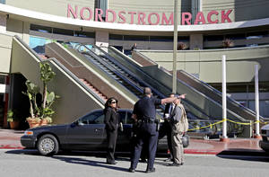 Photo - Los Angeles police investigators stand outside a Nordstrom Rack store at Howard Hughes Center near Los Angeles International Airport Friday, Jan. 11, 2013. Robbers stabbed a clothing store employee and sexually assaulted another during an hours-long hostage drama that ended early Friday with a police SWAT team surging into the shop and rescuing 14 workers. No robbers had been found by mid-morning. The ordeal began at about 11 p.m. when a man called 911 and reported that his girlfriend had called and said there were gunmen in the store, Lt. Andy Neiman said. (AP Photo/Reed Saxon)