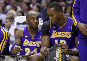Photo - Los Angeles Lakers guard Kobe Bryant, left, draws a play for center Dwight Howard as they sit on the bench in the first half of an NBA basketball game against the Indiana Pacers in Indianapolis, Friday, March 15, 2013.  (AP Photo/Michael Conroy)