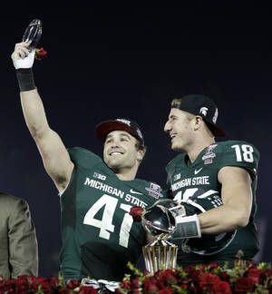 Photo - Michigan State linebacker Kyler Elsworth, left, celebrates with quarterback Connor Cook after Michigan State defeated Stanford 24-20 in the Rose Bowl NCAA college football game on Wednesday, Jan. 1, 2014, in Pasadena, Calif. (AP Photo/Jae C. Hong)