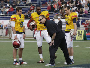 photo - Senior Bowl South Squad quarterback Tyler Wilson of Arkansas (8), EJ Manuel of Florida State (3) and Landry Jones of Oklahoma (14) take direction from Detroit Lions offensive coordinator Scott Linehan during Senior Bowl football practice at Ladd-Peebles Stadium in Mobile, Ala., Wednesday, Jan. 23, 2013.(AP Photo/Dave Martin)