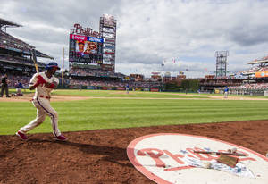 Photo - Philadelphia Phillies' Jimmy Rollins warms up before his at bat during the sixth inning of a baseball game against the Chicago Cubs, Saturday, June 14, 2014, in Philadelphia. The Phillies won 7-4. (AP Photo/Chris Szagola)