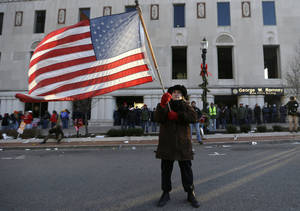 Photo - Protester Paula Merwin, of Leslie, Mich., stands with an American flag Tuesday outside the George W. Romney State Building, where Gov. Rick Snyder has an office, in Lansing, Mich. AP Photo