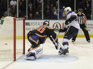 Photo - St. Louis Blues' Kevin Shattenkirk (22) shoots the puck past New York Islanders goalie Kevin Poulin (60) to score the winning goal during a shootout in an NHL hockey game on Saturday, Jan. 25, 2014, in Uniondale, N.Y. The Blues won 4-3. (AP Photo/Kathy Kmonicek)