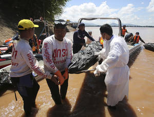 Photo - Thai rescuers unload a plane crash victim's body from a boat in Pakse, Laos Friday, Oct. 18, 2013. Lao Airlines flight QV301 crashed Wednesday as it prepared to land in stormy weather at Pakse Airport in southern Laos. All 49 people on board, more than half of whom were foreigners, are presumed dead. (AP Photo/Sakchai Lalit)