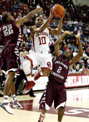 Photo - Oklahoma Sooners' Jordan Woodard (10) splits Oklahoma Christian defenders Nick Tate and Kendre Talley (2) as the University of Oklahoma Sooner (OU) men play the Oklahoma Christian Eagles in an exhibition, college basketball game at McCasland Field House on Monday, Nov. 4, 2013  in Norman, Okla. Photo by Steve Sisney, The Oklahoman