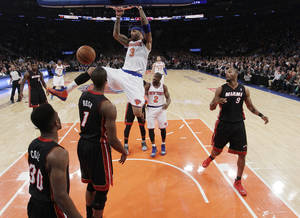 Photo - New York Knicks' Kenyon Martin (3) holds onto the rim after dunking the ball in front of Miami Heat's Chris Bosh (1) and Norris Cole (30) during the first half of an NBA basketball game on Thursday, Jan. 9, 2014, in New York. (AP Photo/Frank Franklin II)