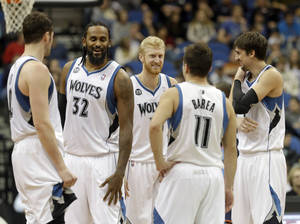 Photo - Minnesota Timberwolves' Kevin Love, left, joines backup players Ronny Turiaf (32) of France, Chase Budinger, J.J. Barea (11) and Alexey Shved, right, of Russia, during a play review in the second half of an NBA basketball game against the Charlotte Bobcats, Friday, Jan. 10, 2014, in Minneapolis.The Timberwolves won 119-92. (AP Photo/Jim Mone)