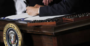 photo - Twenty-two pens are shown next to President Barack Obama as he signs the health care reform bill March 23, 2010, in the East Room of the White House in Washington.  \AP Archives Photo