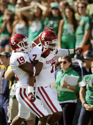 Photo - Oklahoma's Eric Striker (19) and Corey Nelson (7) celebrate an interception returned for a touchdown by Nelson in the first quarter during a college football game between the University of Oklahoma Sooners (OU) and the Notre Dame Fighting Irish at Notre Dame Stadium in South Bend, Ind., Saturday, Sept. 28, 2013. Photo by Nate Billings, The Oklahoman