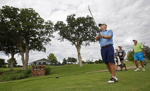 Photo - Lee Symcox, an Oklahoma City native, tees off on a hole near temporary buildings that have been erected on the course at Oak Tree National Country Club in preparation for the 2014 U.S. Senior Open, held in July, on June 12, 2014. Photo by KT King/The Oklahoman