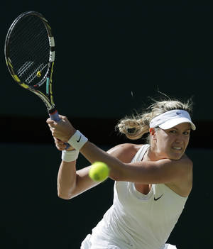 Photo - Eugenie Bouchard of Canada plays a return to Simona Halep of Romania during their women's singles semifinal match at the All England Lawn Tennis Championships in Wimbledon, London, Thursday, July 3, 2014. (AP Photo/Pavel Golovkin)