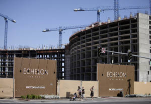 Photo - FILE - This May, 2009 file photo shows people walking past the construction site of Boyd Gaming's Echelon project in Las Vegas.  In a Wednesday, May 7, 2014 licensing hearing before gambling regulators, Malaysian conglomerate Genting Group unveiled new details about its planned Resorts World development at the less-trafficked north end of the Strip. (AP Photo/Jae C. Hong, File)