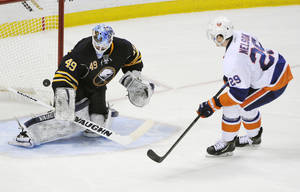 Photo - Buffalo Sabres goaltender Connor Knapp (49) gets beat as New York Islanders  center Brock Nelson (29) scores the game winning goal during the team shootout of an NHL hockey game in Buffalo, N.Y., Sunday April 13, 2014. New York won 4-3. (AP Photo/Gary Wiepert)