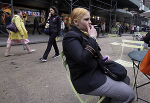 Photo - Amanda Perez smokes a cigarette in New York's Herald Square. Monday, a new law went into effect banning smoking in New York City's urban parks and other public places. The law will be enforced with a $50 fine per violation.AP Photo