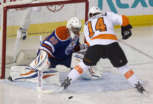 Photo - Philadelphia Flyers' Sean Couturier (14) is stopped by Edmonton Oilers goalie Ilya Bryzgalov (80) during second period NHL hockey action in Edmonton, Alberta, on Saturday, Dec. 28, 2013. (AP Photo/The Canadian Press, Jason Franson)