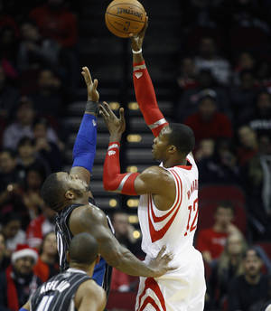 Photo - Houston Rockets power forward Dwight Howard (12) shoots over Orlando Magic power forward Glen Davis (11)during the first quarter of an NBA basketball game Sunday, Dec. 8, 2013, in Houston. (AP Photo/Bob Levey)