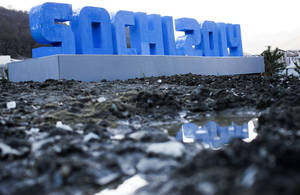 Photo - A Sochi 2014 logo of the 2014 Winter Olympics standing on mud and rubble in front of snow-covered mountains is reflected in a puddle, Monday, Feb. 3, 2014, in Krasnaya Polyana, Russia. (AP Photo/Gero Breloer)