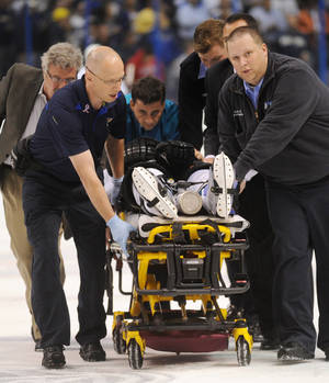 Photo - San Jose Sharks' Dan Boyle, on stretcher, is taken from ice during the first period of an NHL hockey game against the St. Louis Blues on Tuesday, Oct. 15, 2013, in St. Louis. (AP Photo/Bill Boyce)