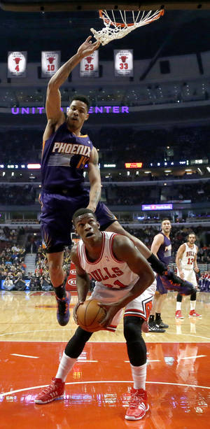 Photo - Chicago Bulls guard Jimmy Butler, right, waits for Phoenix Suns guard Gerald Green (14) to clear the area before scoring during the first half of an NBA basketball game, Tuesday, Jan. 7, 2014, in Chicago. (AP Photo/Charles Rex Arbogast)