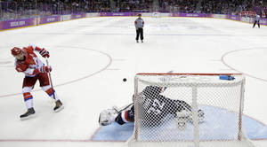 Photo - USA goaltender Jonathan Quick stops the last shot by Russia forward Ilya Kovalchuk in a shootout in the men's ice hockey game at the 2014 Winter Olympics, Saturday, Feb. 15, 2014, in Sochi, Russia. (AP Photo/Mark Humphrey )