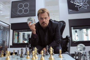 """Photo -   This undated publicity photo released by Muse/IFC shows Eddie Izzard, as crime lord Tannhauser, playing a little game of chess with someone known as God in IFC's new action comedy """"Bullet In The Face."""" The series mixes darkly madcap humor, a silly but sadistic antihero and lots of violence in a stew that even Spencer is hard-pressed to define. (AP Photo/Muse/IFC, Philippe Bosse)"""