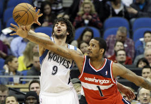 Photo - Minnesota Timberwolves' Ricky Rubio, left, of Spain, and Washington Wizards' Trevor Ariza compete for the loose ball in the first half of an NBA basketball game on Wednesday, March 6, 2013, in Minneapolis. (AP Photo/Jim Mone)