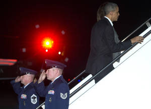 Photo - President Barack Obama and first lady Michelle Obama board Air Force One, Friday, Dec. 20, 2013, in Andrews Air Force Base, Md., en route to Hawaii for their annual family vacation. (AP Photo/Carolyn Kaster)