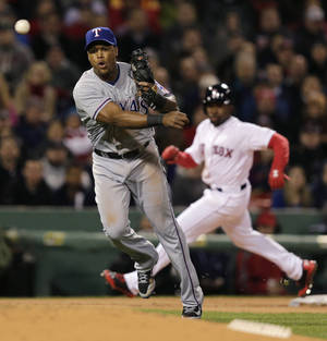 Photo - Texas Rangers third baseman Adrian Beltre, left, makes the throw on a bases loaded ground out by Boston Red Sox's Dustin Pedroia to end  the second inning of a MLB American League baseball game at Fenway Park, Monday, April 7, 2014, in Boston. At rear rounding third is Red Sox Jackie Bradley Jr. (AP Photo/Charles Krupa)