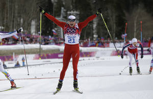 Photo - Switzerland's Dario Cologna crosses the finish line to win the men's cross-country 30k skiathlon at the 2014 Winter Olympics, Sunday, Feb. 9, 2014, in Krasnaya Polyana, Russia. (AP Photo/Gregorio Borgia)
