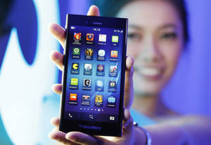 Photo - A Blackberry Z3 smartphone is shown by a model during its launch in Jakarta, Indonesia, Tuesday, May 13, 2014. The Z3 is priced at (US$200) in the country. (AP Photo/Achmad Ibrahim)
